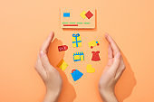 cropped view of female hands around icons near credit card template on peach background