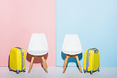 wooden chairs and travel bags on pink and blue background