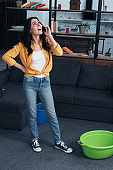 Woman in jeans talking on phone and looking at leaking ceiling
