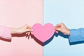 cropped view of man and woman holding heart-shaped card on pink and blue background