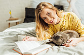 beautiful young woman looking at camera and holding book while lying in bed with scottish fold cat