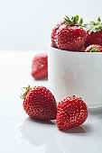 delicious red sweet strawberries in cup on white background