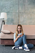 young girl smiling, using smartphone and sitting near sofa
