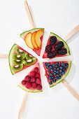 top view of tasty watermelon on sticks with seasonal berries and fruits in circle