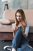 young upset woman using smartphone and sitting near sofa