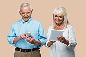 happy retired man using smartphone near wife with digital tablet isolated on beige