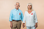 senior couple with red ribbons as hiv awareness holding hands on beige