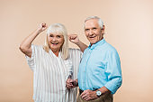 cheerful senior woman gesturing near happy husband on beige