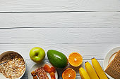 top view of breakfast cereal in bowl, nuts, crispbread and ripe fruits on wooden white background with copy space