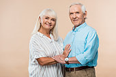 cheerful senior couple smiling while standing on beige