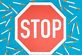 Studio shot of big stop sign with cigarettes isolated on blue, stop smoking concept