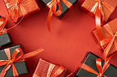 top view of gift boxes with bows and ribbons on red background with copy space