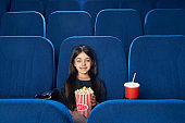 Front view of cute brunette enjoying film in cinema