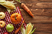top view of checkered tablecloth with pumpkin, sweet corn, apples and carrots on wooden surface with copy space