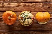 top view of various fresh pumpkins on wooden surface with copy space