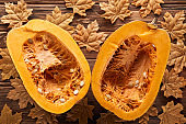 top view of ripe pumpkin halves on brown wooden surface with dry autumn leaves