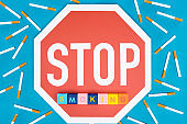 Top view of stop sign, cigarettes and blocks with letters isolated on blue, stop smoking concept