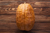 top view of long ripe pumpkin on brown wooden surface