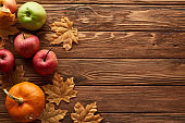 top view of small pumpkin and apples on brown wooden surface with dried autumn leaves