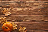 top view of small pumpkin on brown wooden surface with dried autumn leaves