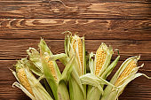 top view of uncooked sweet corn on wooden surface with copy space