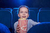 Excited girl eating popcorn and watching amazing film