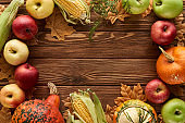 top view of frame of pumpkins, sweet corn and apples on wooden surface with dried autumn leaves