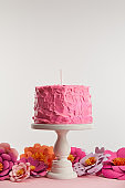 pink birthday cake with candle on cake stand near paper flowers on grey