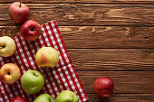 top view of checkered tablecloth with fresh apples on wooden surface with copy space