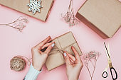 cropped view of girl packing christmas presents with craft paper, twine and flowers, isolated on pink