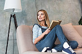 young woman looking away and sitting on sofa with book
