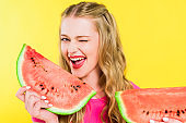 beautiful girl with watermelon winking Isolated On yellow