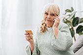 confused retired woman holding credit card while talking on smartphone