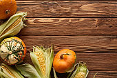 top view of raw pumpkins and sweet corn on brown wooden surface
