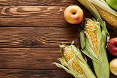 top view of fresh apples and sweet corn on brown wooden surface