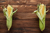 top view of fresh corn on wooden surface with copy space