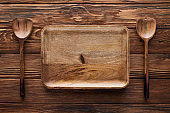 top view of empty rectangular dish between spoons on brown wooden surface with copy space
