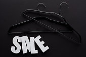 top view of white sale lettering with hangers on black background