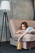 young woman thinking, holding book in hand and lying on sofa