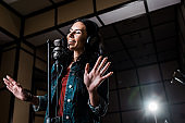 attractive inspired woman singing near microphone in recording studio