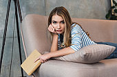 beautiful girl thinking, holding book and lying on sofa with book