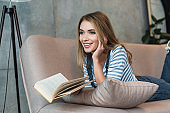 beautiful girl smiling, holding book and lying on sofa with book
