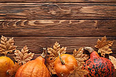 top view of small ripe pumpkins on brown wooden surface with dry autumn leaves