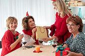 Happiness senior women exchanging Christmas presents