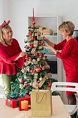 Senior women decorating a Christmas tree