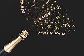 Creative New Year composition with champagne bottle and confetti.