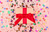 A gift box, champagne glass and confetti on pink background.