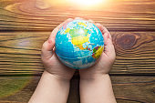 globe in hands in the sun on a wooden background