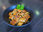 A bowl of grilled unagi nigiri or sushi  over steamed rice topped with white sesame served with pickled ginger and wasabi. Japanese traditional food.