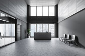 Reception table in gray open space office interior